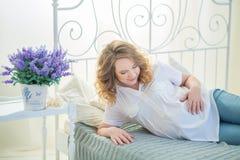 Elternteil-zu-sind die Paare glücklich, die nette rote Babyschuhe nach ihrem ungeborenen Kind, zuhause Studioporträt betrachten Stockbild
