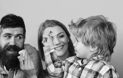 Elternuhrkind, das mit den gelben und blauen Ziegelsteinen spielt Mann mit Bart, Frau und Junge spielen auf blauem Hintergrund Stockfoto