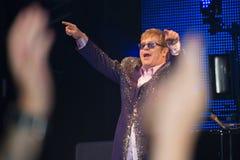 Elton John Live konsert som ses från folkmassan Arkivbild