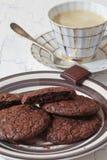 Eluda las galletas del brownie en la placa de la loza y la taza de café foto de archivo
