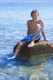 Elva år gammalt pojkesammanträde på en vagga i havet Royaltyfri Bild