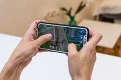 Elva, Estônia - 15 de novembro de 2018: iphone da terra arrendada da menina com jogo em linha de Fortnite na exposição, jogando o foto de stock royalty free