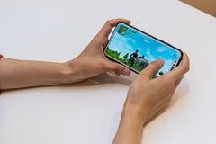 Elva, Estônia - 15 de novembro de 2018: iphone da terra arrendada da menina com jogo em linha de Fortnite na exposição, jogando o fotos de stock royalty free