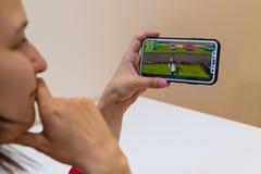 Elva, Estônia - 15 de novembro de 2018: iphone da terra arrendada da menina com jogo em linha de Fortnite na exposição, jogando o foto de stock