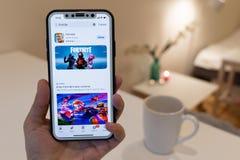 Elva, Estland - November 12, 2018: de hand van het meisje houdt iphone met online Fortnite-spelvoorproef in app opslag op de vert stock foto's