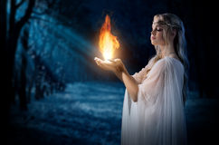 Elven girl holding fire in palms at night forest Royalty Free Stock Images