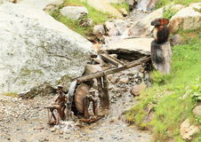 Elves by flum. Wooden statues of elves working on flum wheel drive on small rivulet stock photography