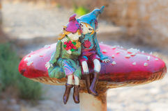 Elves in Love. Two young elves in love sit atop a magic mushroom royalty free stock images