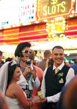 Elvis and a bride and groom in Vegas. Elvis with a happy bride and groom in Las Vegas on historic Fremont Street Experience in the USA Stock Photo