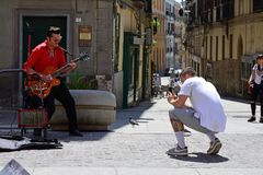 Elvis Impersonating Musician, Cagliari, Sardinia, Italy. Elvis Presley impersonator / busker and singer playing Gretsch guitar outside restaurant on Piazza Yenne Stock Image