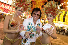 Elvis Presley Impersonator With Casino Dancers. Portrait of happy Elvis Presley impersonator standing with casino dancers Stock Image