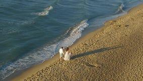 Elvovedpaar die op kust in avondtijd lopen Romantisch paar die holdingshanden wandelen stock videobeelden
