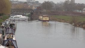Big yellow narrow boat moving along the river. More boats in back ground stock video footage
