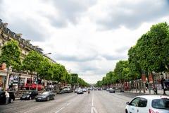 Elysian Fields avenue with street traffic and green trees. Paris, France - June 02, 2017: Elysian Fields avenue with street traffic and green trees on cloudy sky stock photo