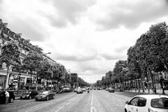Elysian Fields avenue with street traffic and green trees. Paris, France - June 02, 2017: Elysian Fields avenue with street traffic and green trees on cloudy sky stock photos