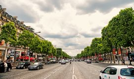 Elysian Fields avenue with street traffic and green trees. Paris, France - June 02, 2017: Elysian Fields avenue with street traffic and green trees on cloudy sky stock images