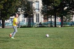 Elysian sätter in Amatörmässiga fotbollgrabbar på gräsmattan royaltyfria bilder