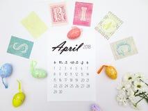 Em abril de 2018 calendário, ovos da páscoa e crisântemos brancos em um fundo branco foto de stock royalty free