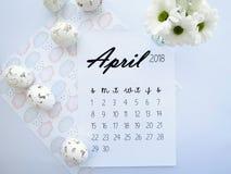 Em abril de 2018 calendário, ovos da páscoa e flores brancas fotografia de stock