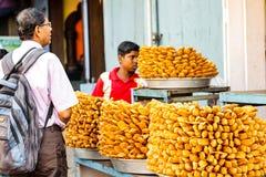 Em abril de 2019, Puri, Orissa, ?ndia Turistas que compram petiscos de Khaja, fritos mergulhados Dunked em Sugar Syrup, para a ve imagem de stock royalty free