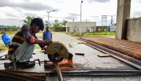 Em agosto de 2018, Kolkata, Índia, um trabalhador masculino que corta a barra de aço com Bosch motorizado Rod Cutter de aço e que imagem de stock