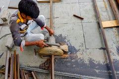 Em agosto de 2018, Kolkata, ?ndia, um trabalhador masculino que corta a barra de a?o com Bosch motorizado Rod Cutter de a?o e que foto de stock