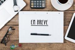 EM-Brevis, portugiesischer Text für das Kommen bald auf Notizblock im Büro Lizenzfreies Stockbild