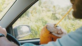 Em-carro do close-up do POV disparado das mãos masculinas com o relógio esperto que conduz o carro, guardando o suco de fruta exó vídeos de arquivo