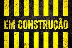 Em Construcao в португалке: Под предупредительным знаком конструкции при желтые и черные нашивки покрашенные над предпосылкой бет Стоковое Изображение