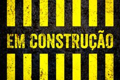 Em Construcao In Portuguese: Under construction warning sign with yellow and black stripes painted over concrete wall background. Concept for do not enter area Stock Image