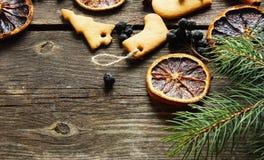 Em cookies de madeira de um Natal do fundo, canela, laranjas, tre Imagens de Stock