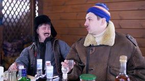 Em homens da casa de campo dois os frieds na roupa do inverno sentam-se em torno da tabela e do riso filme
