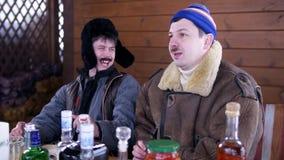 Em indiv?duos da casa dois da vila os amigos sentam-se em torno da tabela completamente do alimento e da vodca da bebida vídeos de arquivo