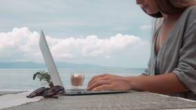 5 em 1 A jovem mulher trabalha no portátil no café exterior video estoque