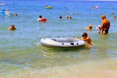 Em julho de 2017 - o menino empurra adiante um barco de borracha na água em Cleopatra Beach Alanya, Turquia Fotografia de Stock Royalty Free