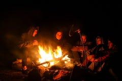 Em outubro de 2014: grupo de amigos que riem e que sentam-se no fogo do acampamento após a caminhada longa da montanha do outono Imagem de Stock