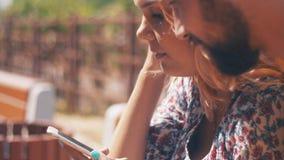 Em pares do amor com o smartphone que senta-se no banco Dia ventoso do verão chatting filme