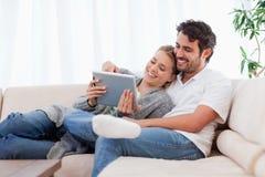 Em pares do amor usando um computador da tabuleta Fotos de Stock Royalty Free