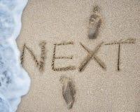 EM SEGUIDA e pegadas na areia encalhe com espuma da onda imagem de stock royalty free
