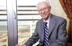 Homem de negócios superior que sorri à câmera Fotografia de Stock Royalty Free