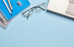 Em um caderno do fundo e em uns artigos de papelaria azuis do escritório imagens de stock royalty free