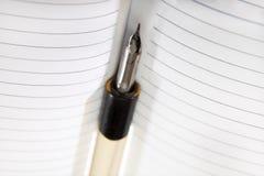 Em um caderno limpo encontra-se um penholder velho com pena Fotografia de Stock Royalty Free