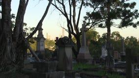 Em um cemitério dilapidado no crepúsculo, uma skyline da cidade reflete o sol de ajuste, zumbir mais visível dentro filme