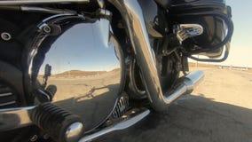Em um cromo bonito chapeou as peças da motocicleta reflete a estrada e a borda da estrada Viagem distante vídeos de arquivo