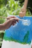 Em um dia ensolarado uma jovem mulher está pintando no parque Foto de Stock Royalty Free