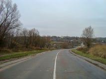 Em um dia nebuloso, a estrada velha corre através do campo foto de stock royalty free