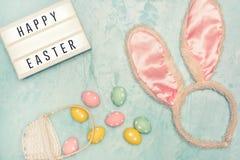 Em um fundo azul é uma cesta com os ovos pequenos coloridos Lightbox com a Páscoa feliz da inscrição Perto das orelhas da foto de stock