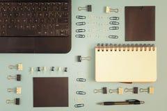 Em um fundo azul, um bloco de notas, uns clipes e uns botões de escritório são arranjados ordenadamente Fundo incomum do negócio  Imagem de Stock