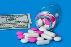 Em um fundo azul, os comprimidos dispersaram de um frasco e de duas contas de cem dólares imagem de stock royalty free