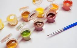 Em um fundo branco há uns assuntos para tirar, uma pintura do guache e uma escova, recipientes com uma pintura multi-colorida Imagens de Stock Royalty Free